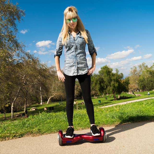 Blonde woman with sunglasses riding red hoverboard in park