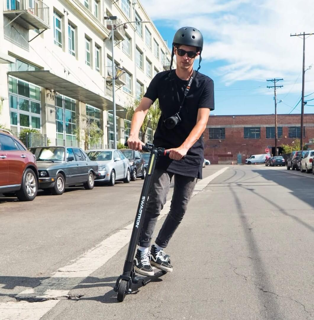 Guy wearing helmet riding a Swagger 2 Electric Scooter