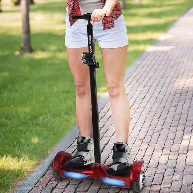 Woman riding hoverboard with handlebar in park