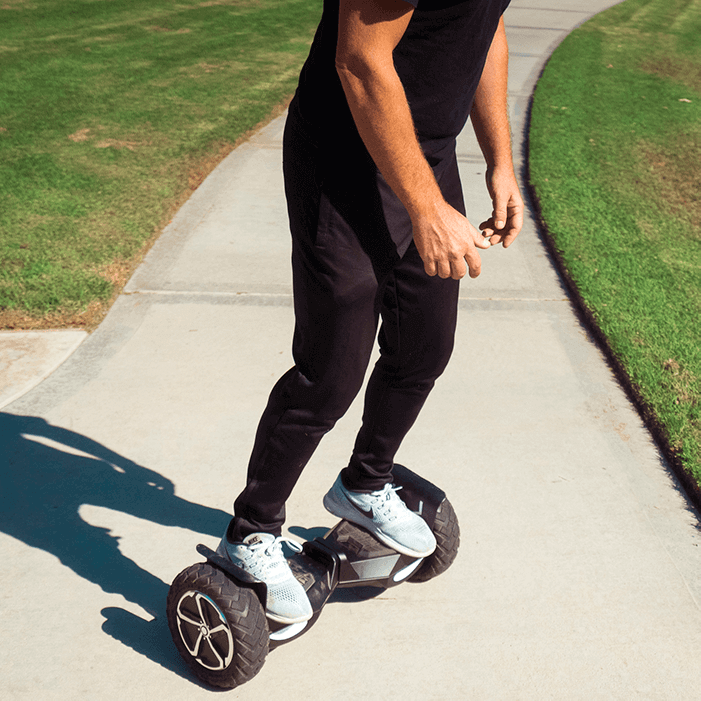 """Adult rides the All-Terrain T6 Hoverboard in the park and through the grass with the 10"""" inch off road hoverboard wheels"""