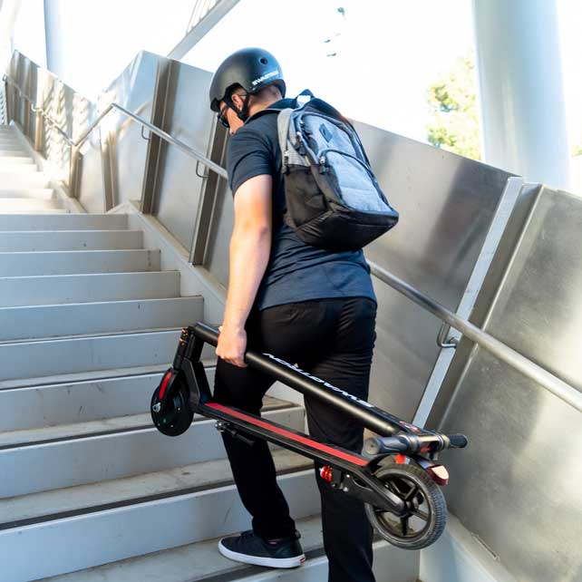 Student carrying foldable electric scooters upstairs on his college campus