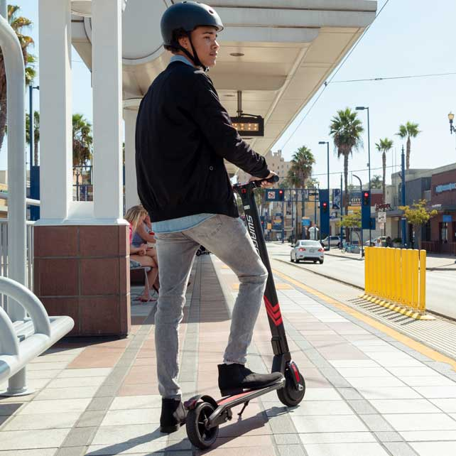Young adult waiting with electric folding scooter at train station