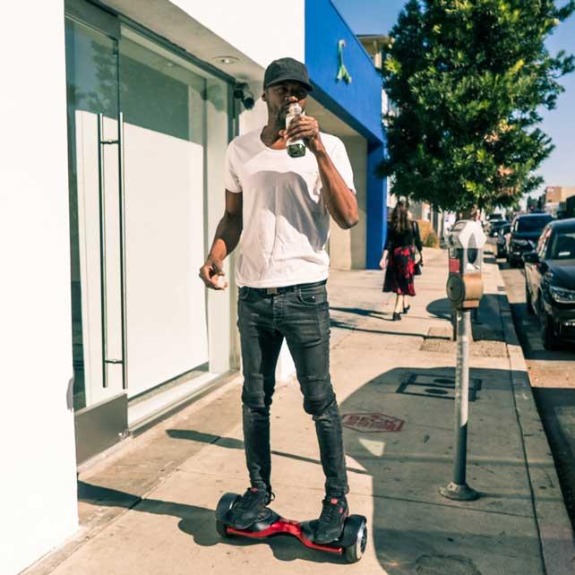 Man drinks juice on red hoverboard on sidewalk.