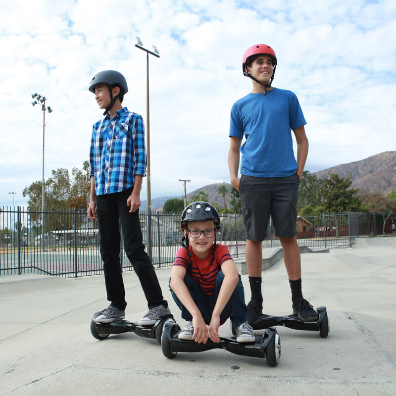 Three teenagers ride their hoverboard in the park while playing and having fun with their swagboard by swagtron