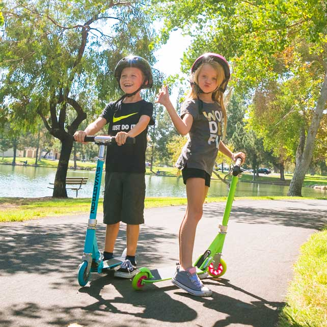 two kids play on green and blue stunt scooters