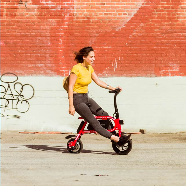 woman with backpack riding red swagcycle