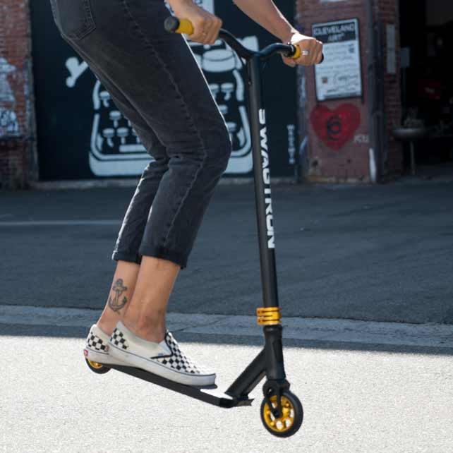 woman with skater shoes on black stunt scooter