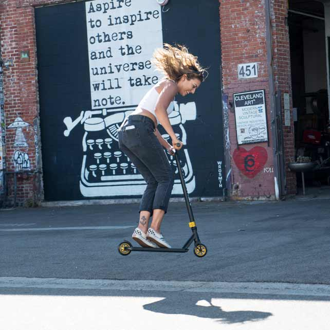 Woman in skater shoes jumps on on stunt scooter
