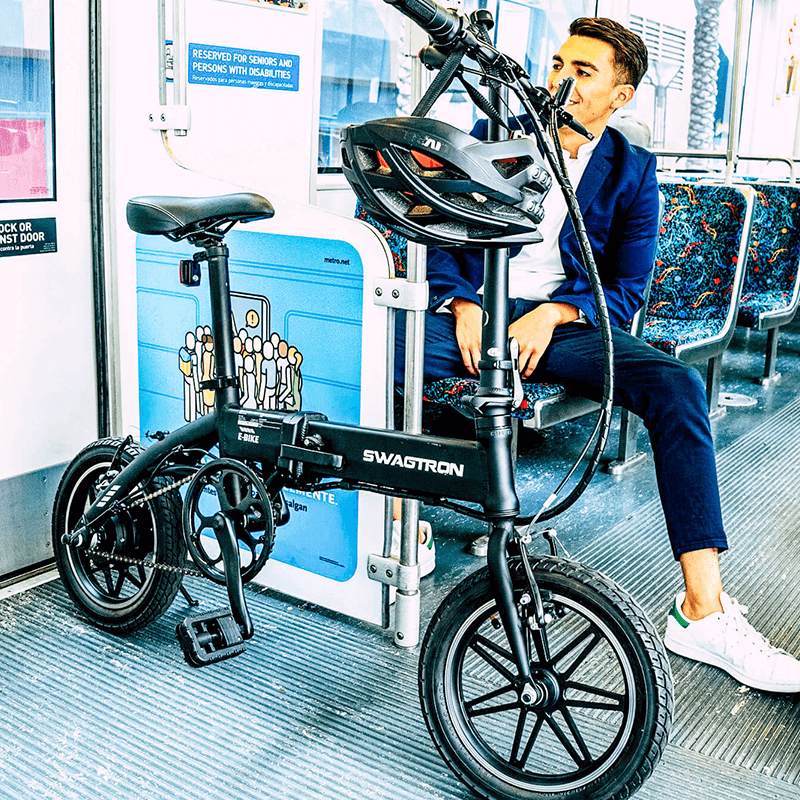 Young professional riding the train with his foldable electric bike, making this electric bicycle ideal for small spaces and city commuters