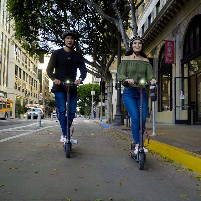 Couple riding scooters in bike lane