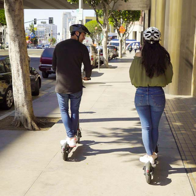 Couple riding scooters on sidewalk in city