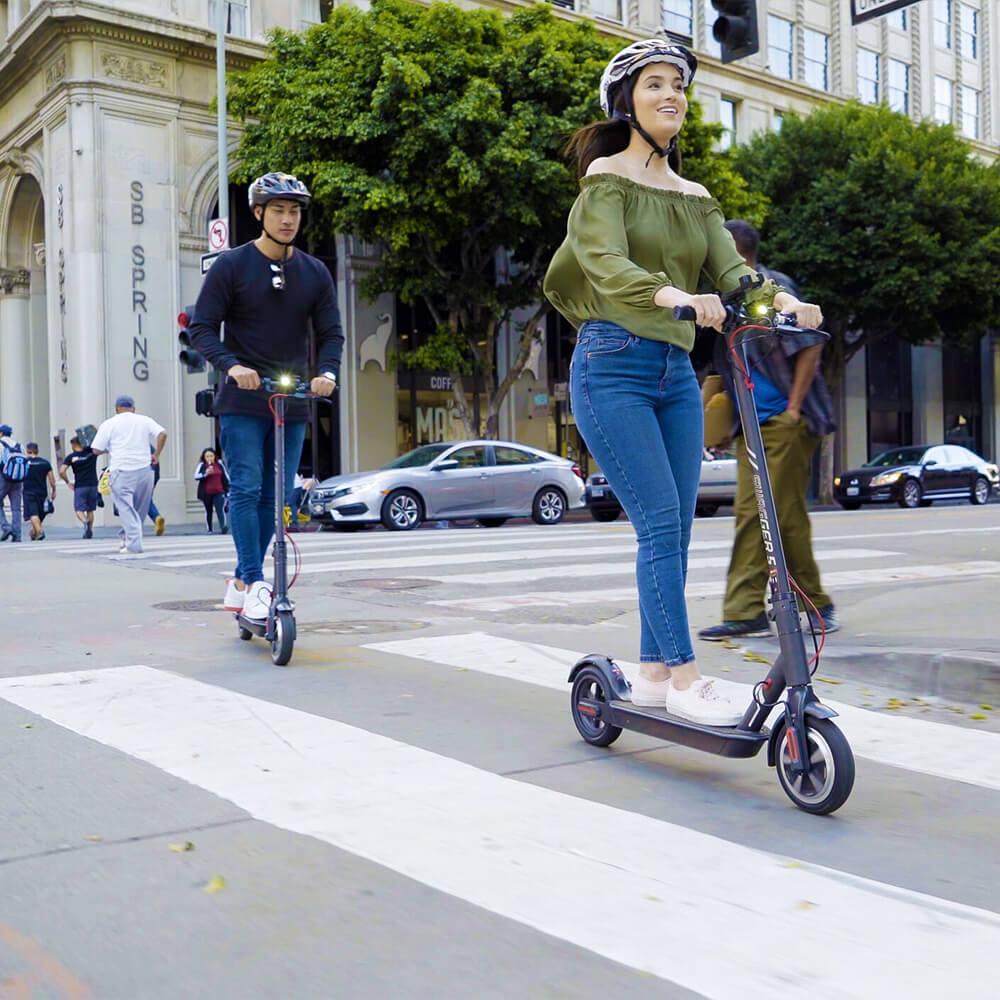 Couple riding their electric scooters around the city