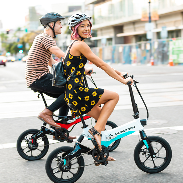 Couple riding their electric foldable e-bike in the city