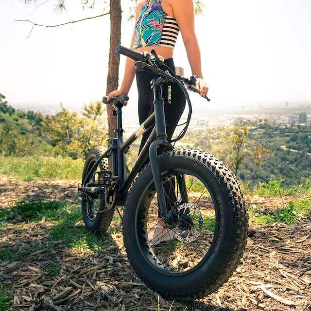 teenage girl next to Swagtron e-bike