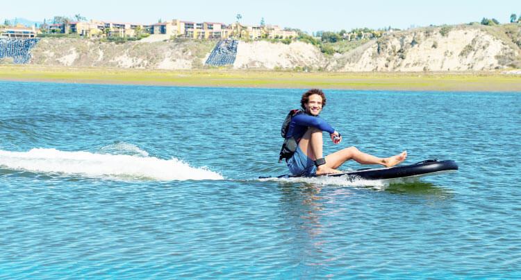 Smiling man sitting on his powered SwagSurf as it makes waves on the lake.