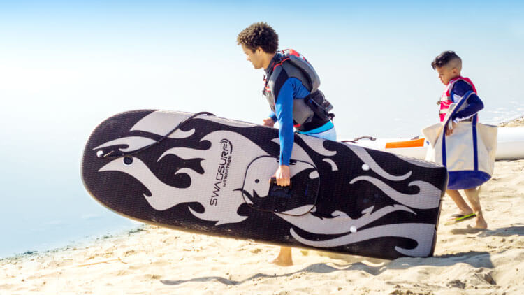 Man carrying his SwagSurf Electric Surf Jetboard to the lake with his son.