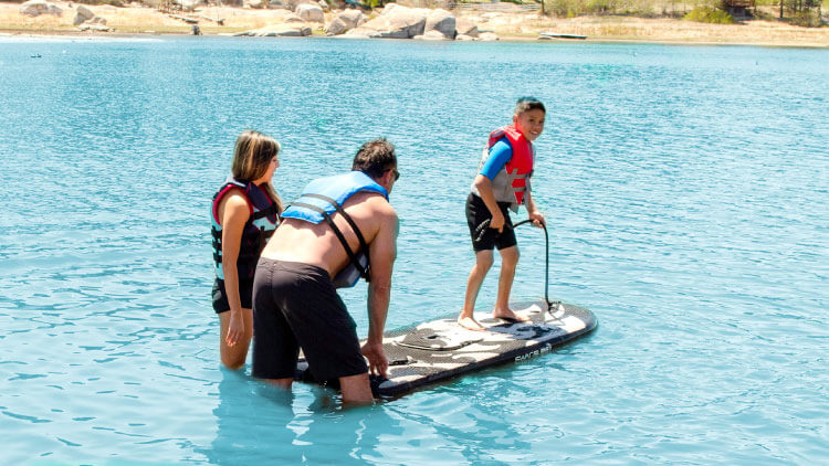 Smiling kid riding his SwagSurf on the lake as his parents look on.