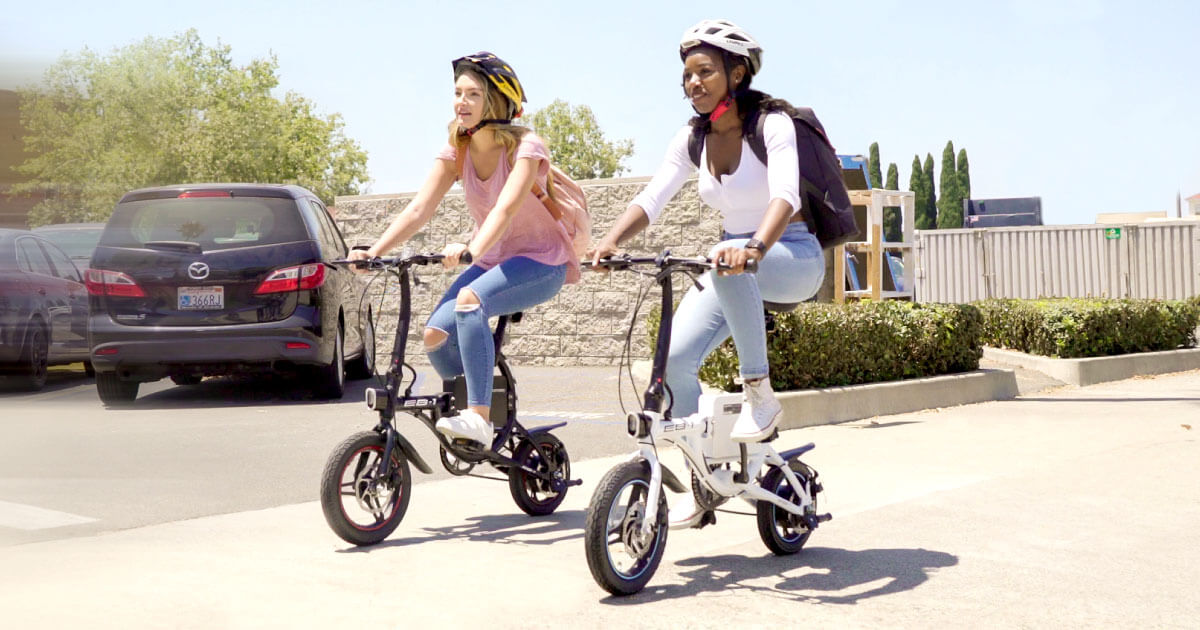 Two women riding their Swagtron EB-1 electric bikes.