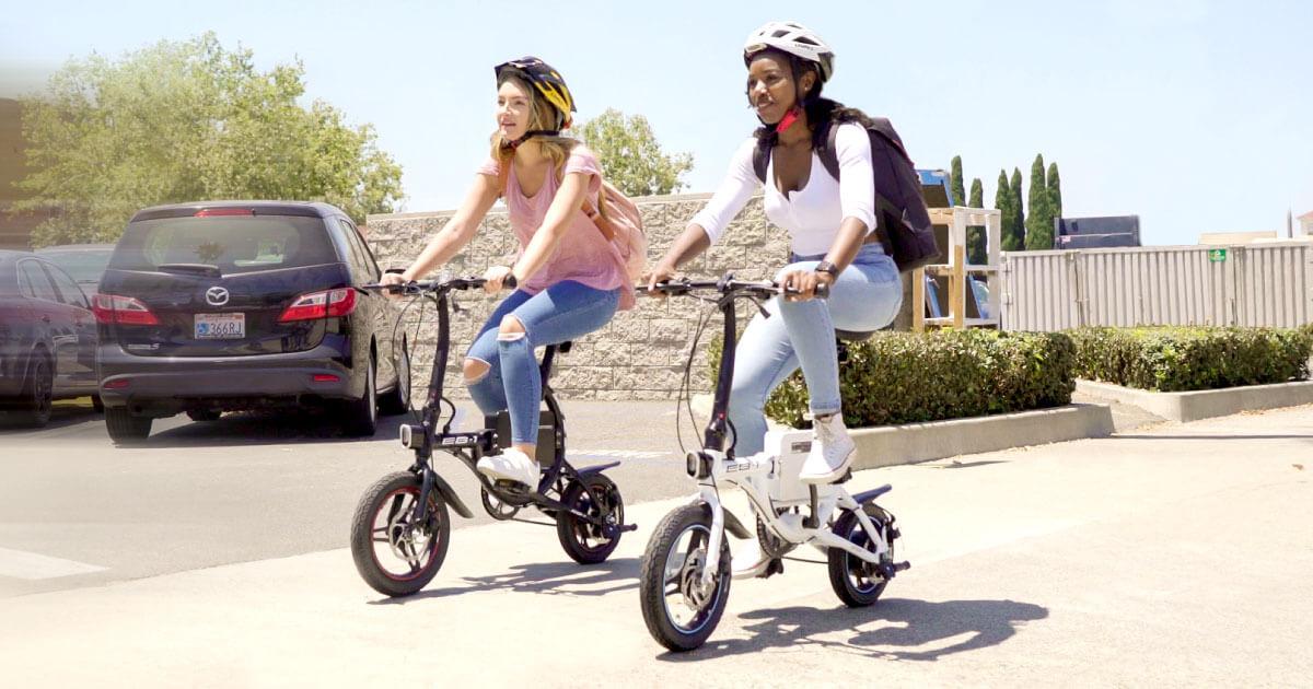Two women riding their Swagtron EB-1 electric bikes.