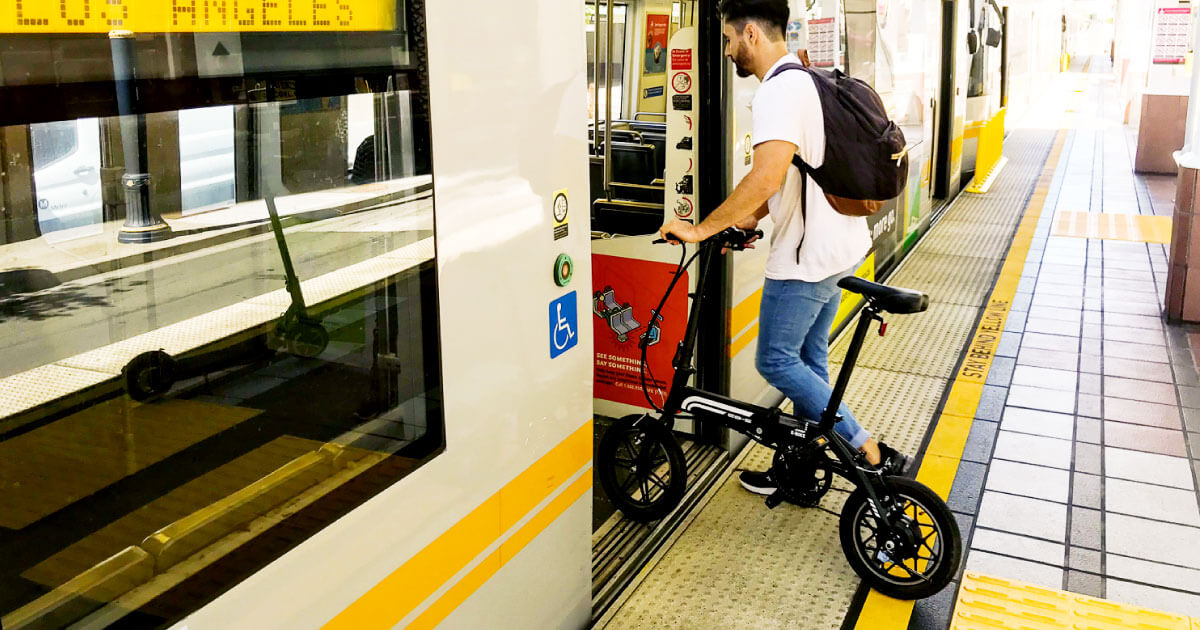 Man stepping on to the train with his Swagtron EB-1 commuter electric bike