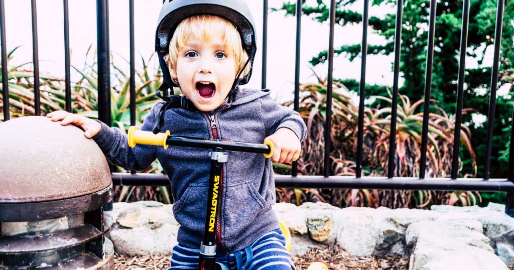 Happy boy riding a Swagtron K2 toddler scooter