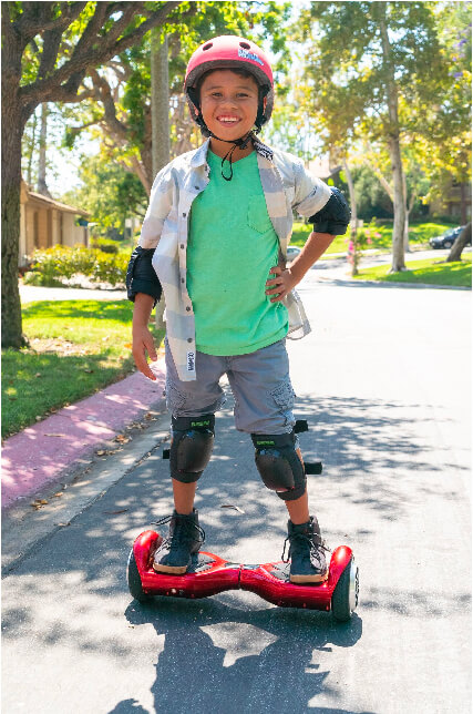 Kid riding his hoverboard in his neighborhood wearing a helmet