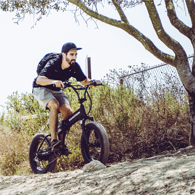 Man climb hills with the Electric Fat Tire All-Terrain Bike; ideal for off roads and trails