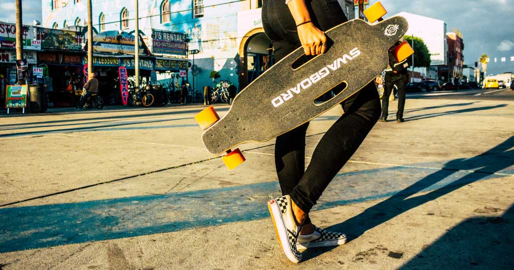 Young lady effortlessly carrying a Swagskate NG1 Electric Skateboard