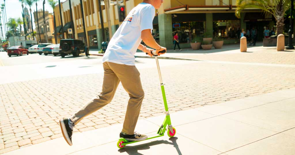 Teen boy riding on a K1 kick scooter