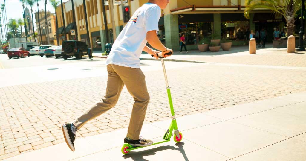 Teen boy riding on a K1 kick scooter