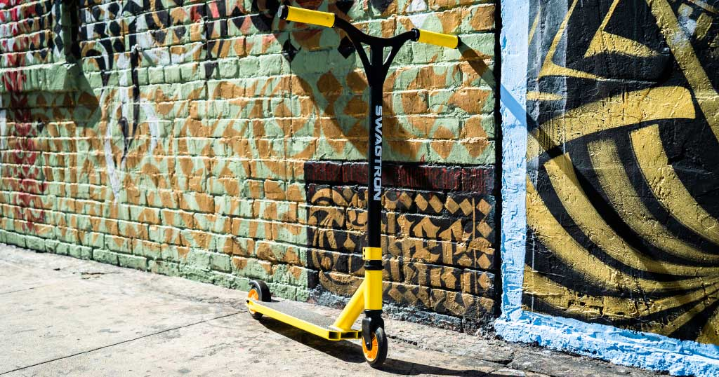Swagtron Classic ST045 stunt scooter leaning against a wall