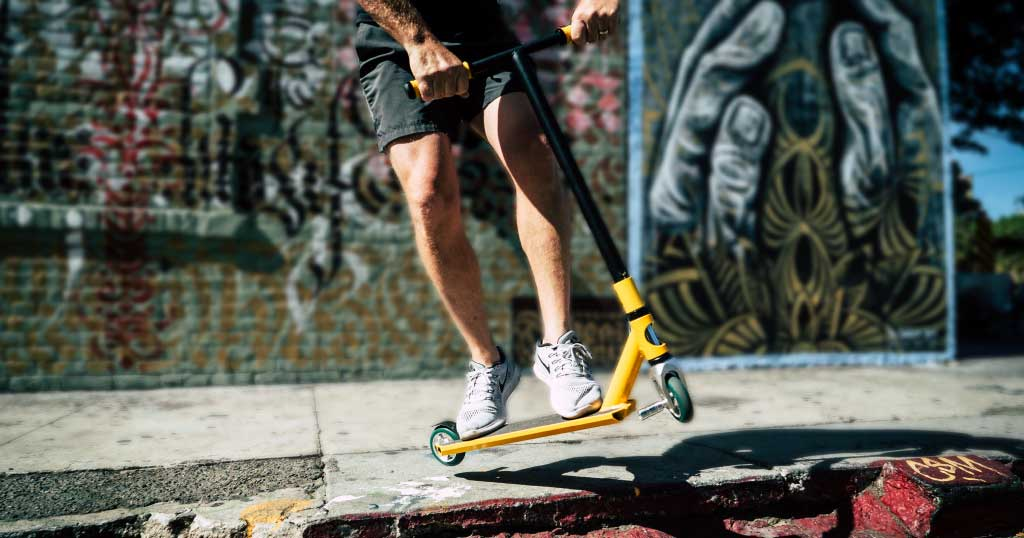 Young male teen performing a scooter stunt on the ST046 Pro Stunt Scooter