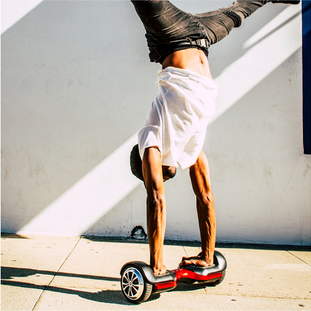 Guy balancing on hands on a Swagboard Vibe T580 hoverboard