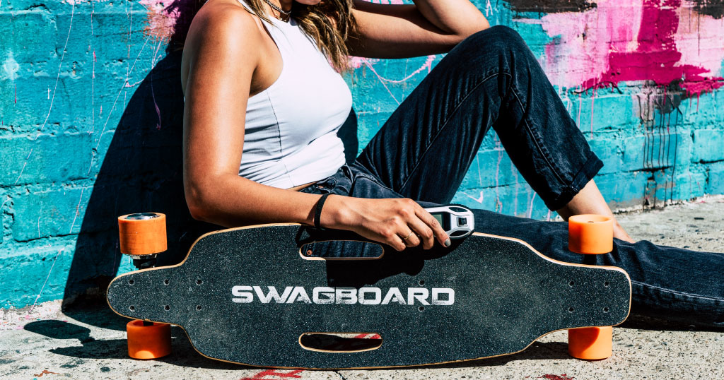 Girl sitting with her Swagskate Classic NG1 electric skateboard