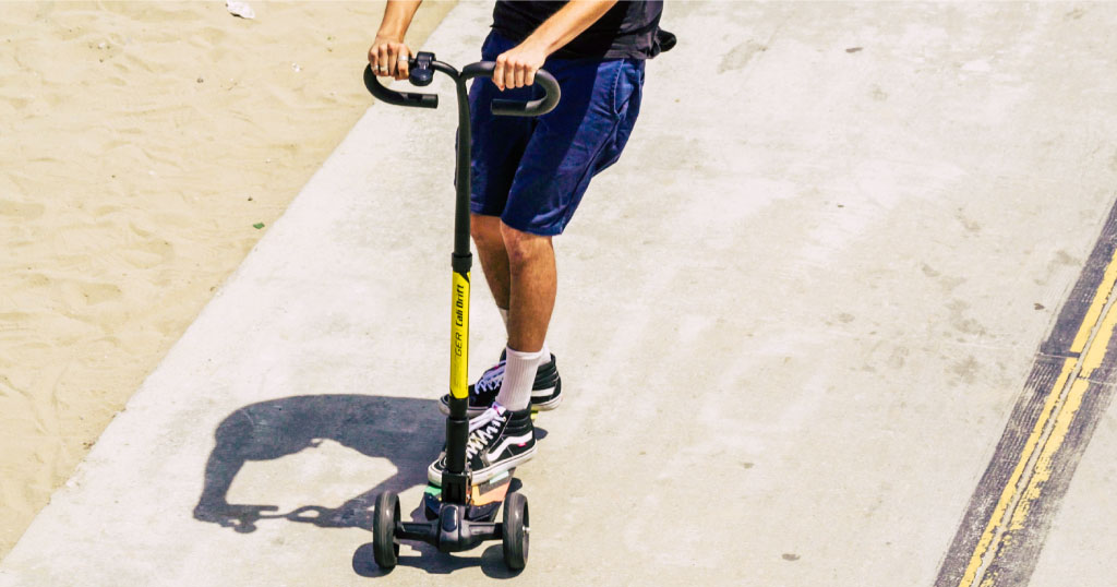 Close up of a young man riding a Swagger Cali Drift three-wheeled electric scooter
