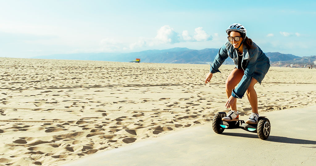 Hoverboard Holiday Guide, Beach-side view of female riding the Swagboard T6 Outlaw