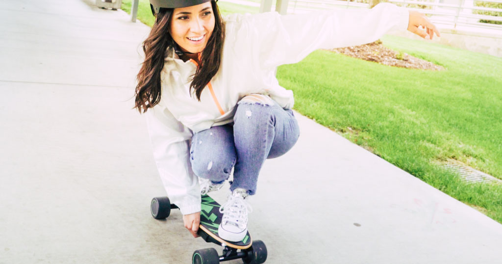 Close up of woman low-riding on her Spectra Mini E-Board