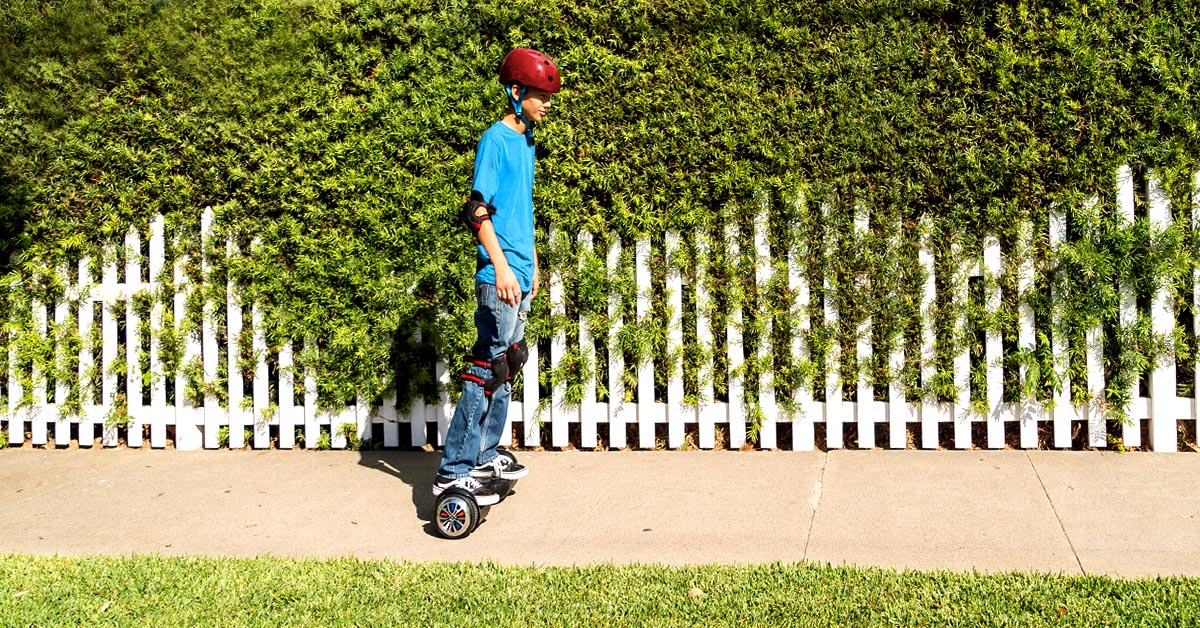 Kid wearing a helmet riding a hoverboard
