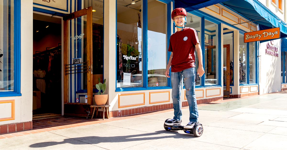 Happy blonde kid wearing a helmet and riding a hoverboard