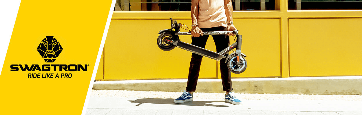 An adult holding a folded electric scooter on a city sidewalk.
