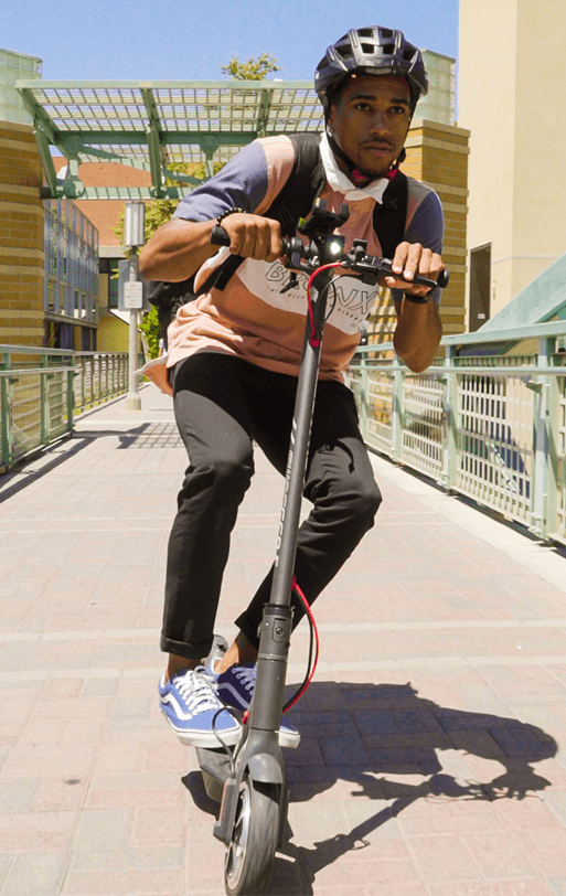 Student rides Electric Scooter on campus on his way to class