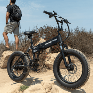 Guy standing by his off road electric bike in a trail