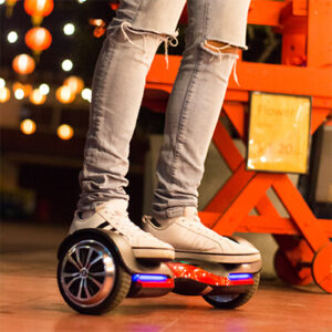 Person riding a red and black hoverboard, model Vibe T580 from Swagtron with Bluetooth