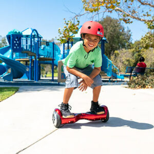 Kid riding his favorite red hoverboard in the park