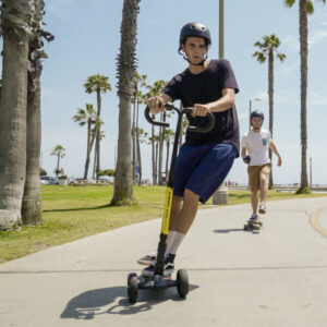 Man riding his cali drift three-wheel electric scooter near the beach