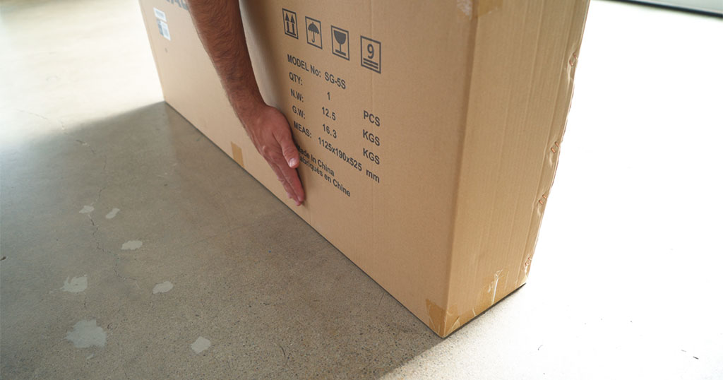 Man taking his first steps with the Swagger 5 by inspecting the box for carrier damage