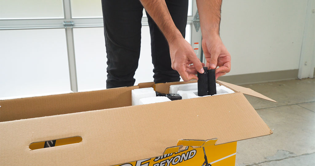 Close-up of man taking contents out of the b Swagger 5 box for assembly.