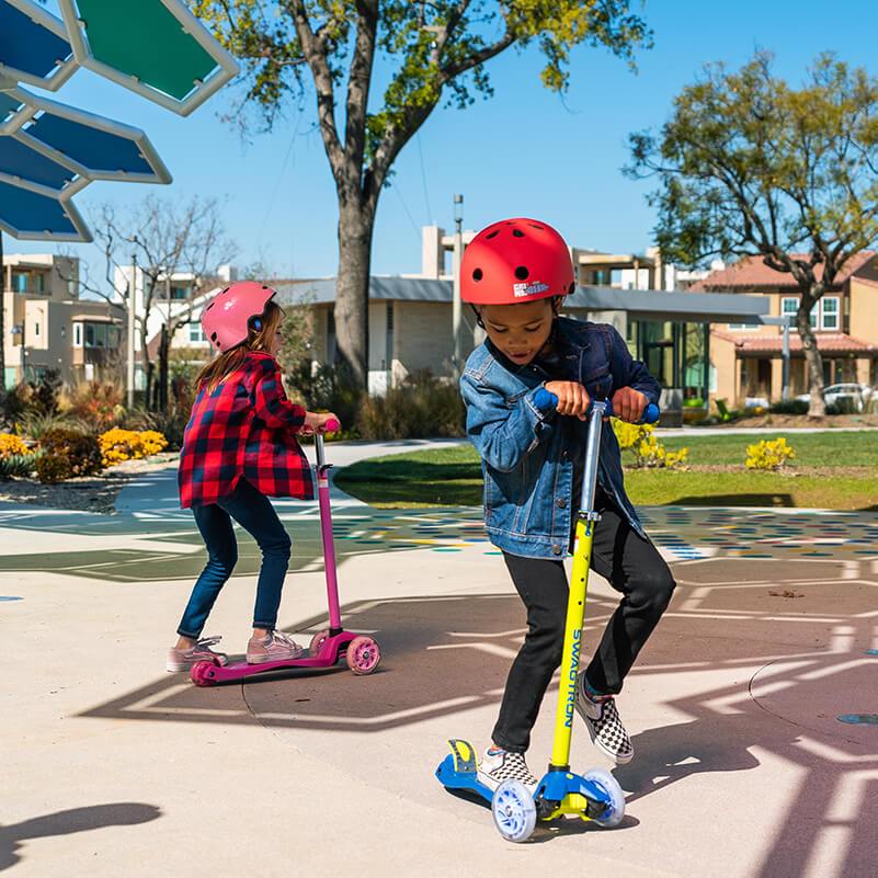 Boy and girl riding their three-wheel scooters at the park while having fun during playtime