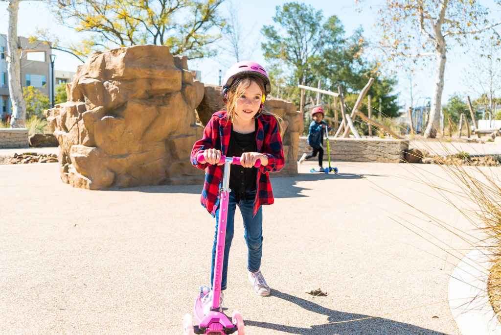 Young girl wearing a helmet, riding a K5 three-wheel scooter.