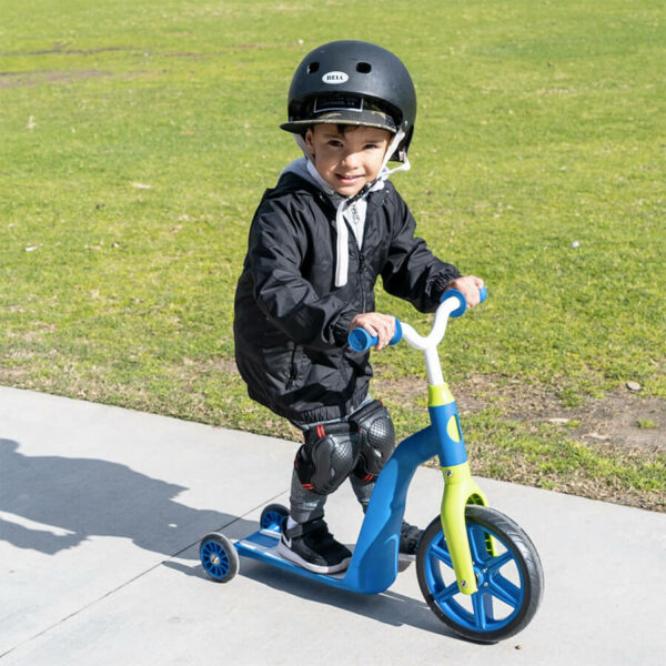 Young child with a helmet on riding a kids swagtron k6 scooter on the sidewalk